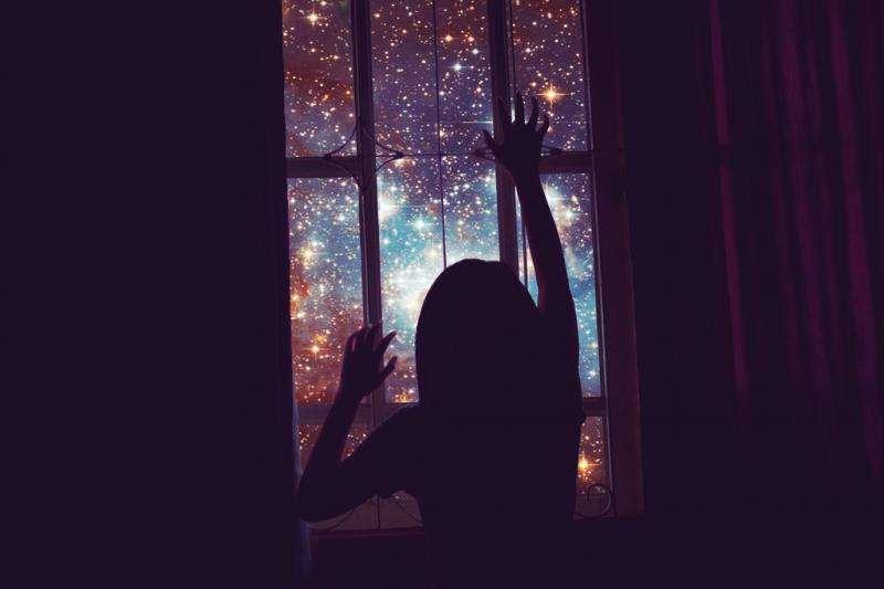 Γυναίκα κοιτάει τα αστέρια από το παράθυρο